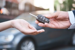 photo of dealer passing key for car rental
