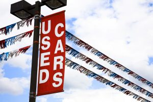 'Used Cars' sign over a vehicle dealership car lot. Red. Clouds in sky.